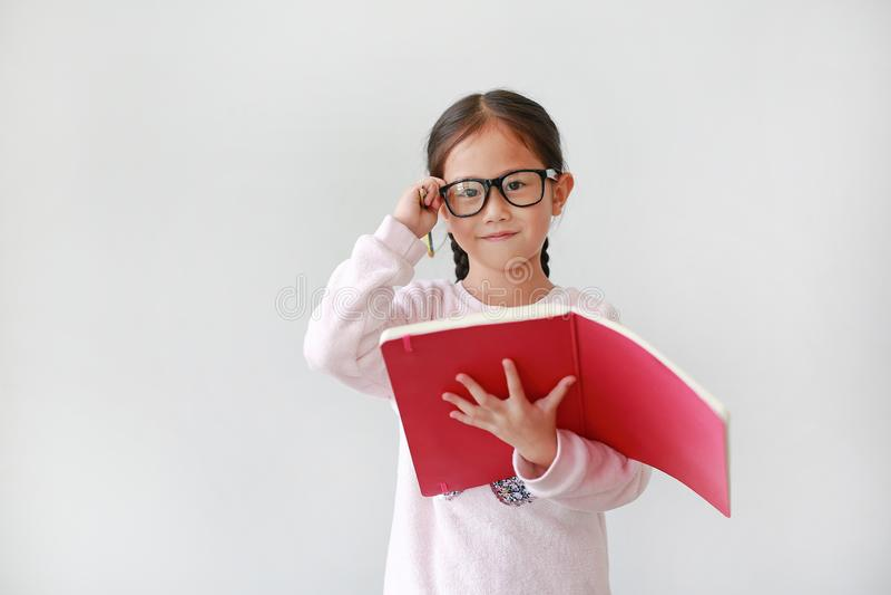 小亚裔女小学生佩带的镜片和举行笔记本画象有铅笔的在白色背景 库存图片