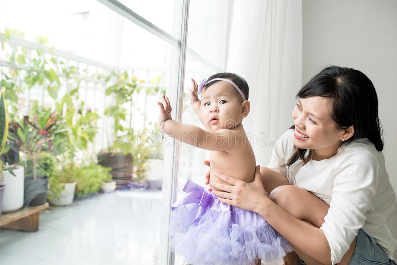 小亚裔女婴在绝尘室在家站立近的窗口 库存照片