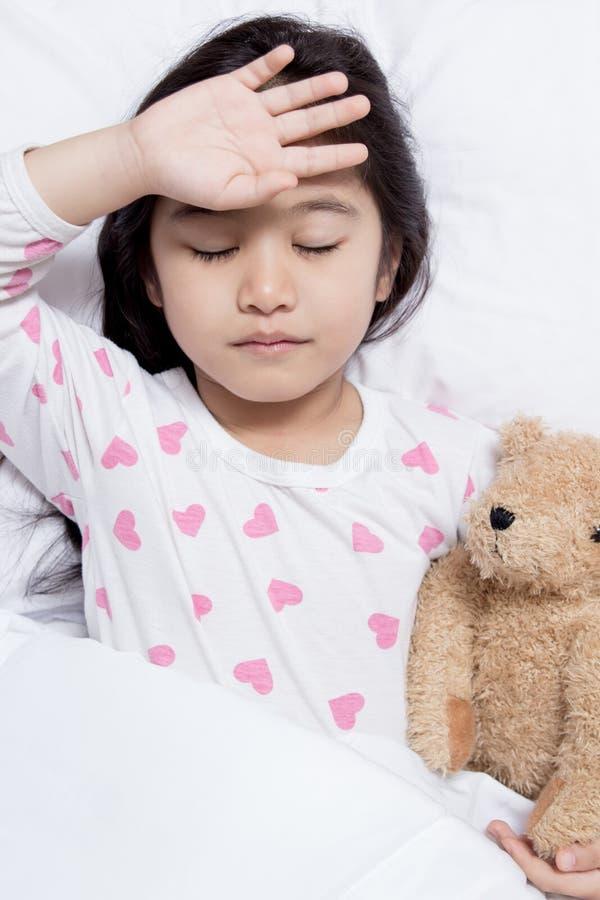 小亚裔孩子有热病和放置在床上 免版税库存图片