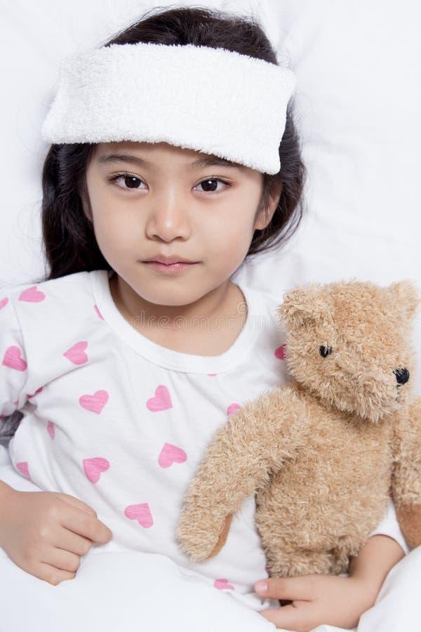 小亚裔孩子有热病和放置在床上 库存图片