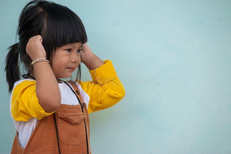 小亚裔孩子,佩带棕色围嘴的女孩举您的手,关闭您的耳朵,不要听见 图库摄影