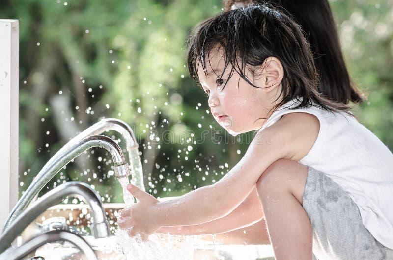 小亚裔婴孩洗涤的手 库存照片