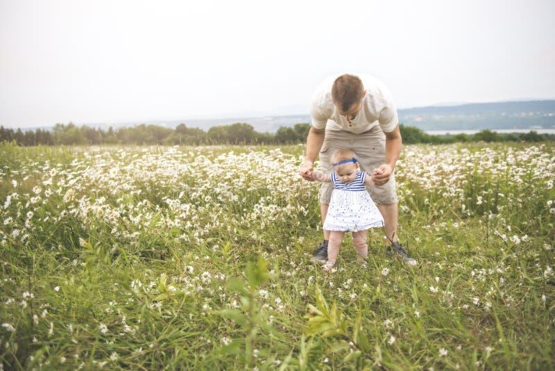 小享用户外在雏菊花的领域的女婴和他的父亲 免版税库存照片
