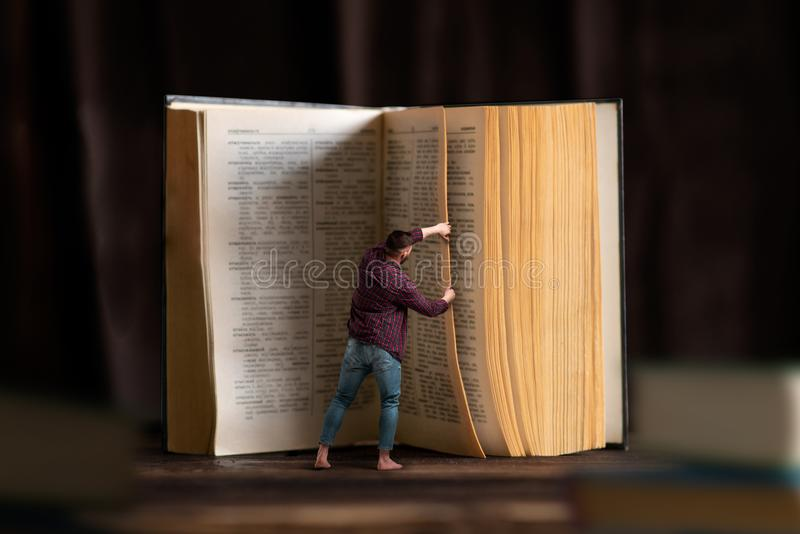 小人转动大书页,读 免版税库存图片