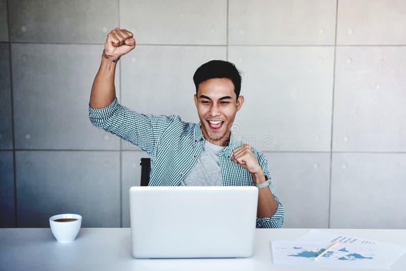 小企业和成功的概念 高兴年轻亚洲的商人接受喜讯或高赢利 免版税图库摄影