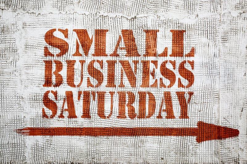 小企业在灰泥墙壁上的星期六街道画 免版税库存图片