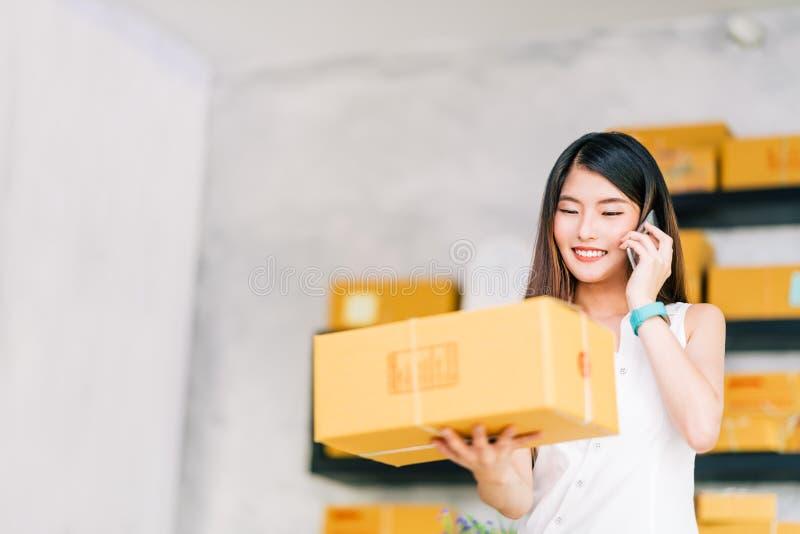 小企业主,亚洲妇女举行包裹箱子,使用收到购买订单的手机电话,在家运作办公室 免版税库存图片