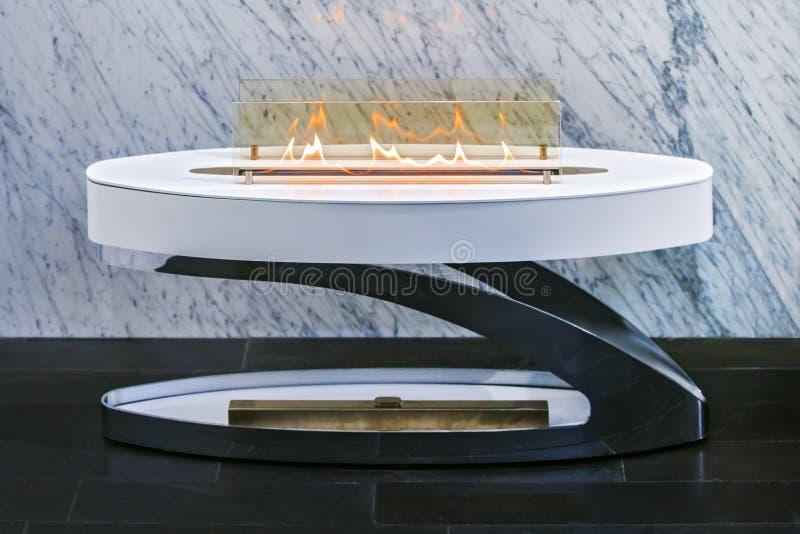 小便携式的时兴的壁炉,在大理石墙壁背景的白色现代壁炉  库存图片