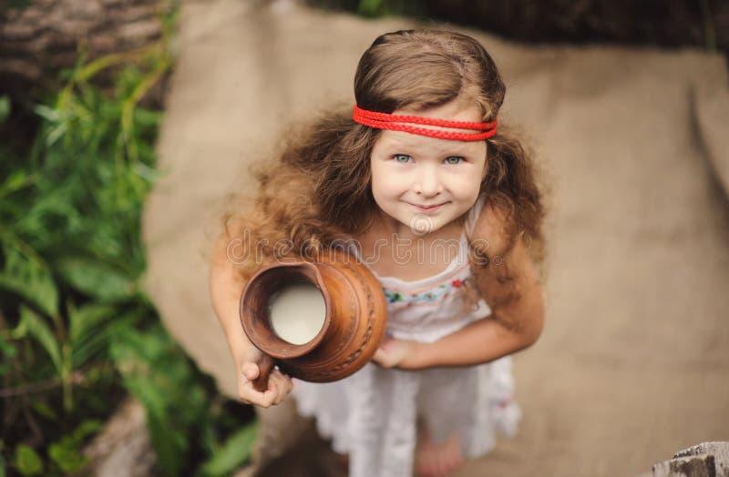 小俏丽的女孩在绿色庭院里 免版税图库摄影