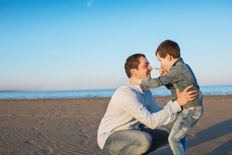 小儿子微笑给他的父亲并且显示他的手指给他在海滩 库存图片