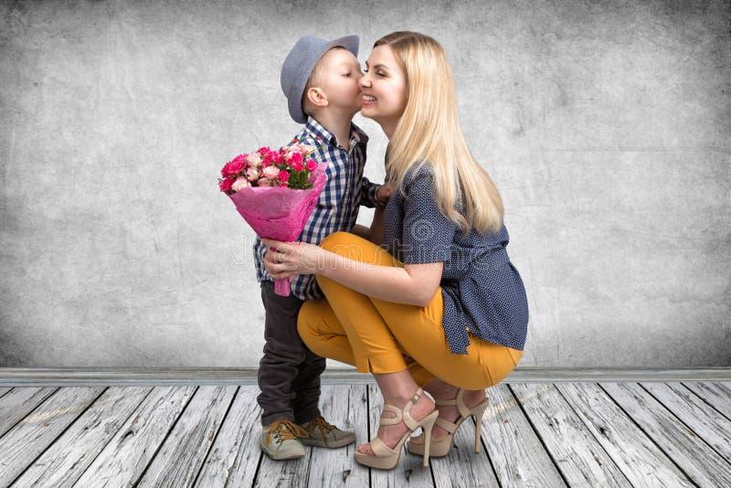 小儿子给他心爱的母亲桃红色玫瑰美丽的花束并且亲吻面颊的妈咪 春天,妇女的天,母亲节 免版税库存图片