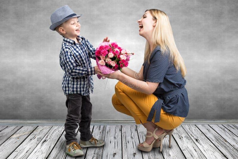 小儿子给他心爱的母亲桃红色玫瑰美丽的花束  春天,家庭度假的概念 妇女` s天,母亲` s da 免版税库存图片