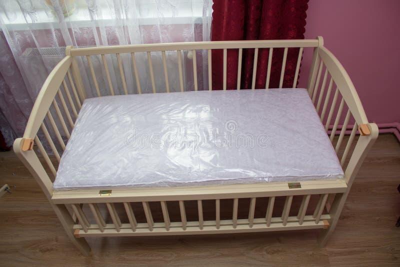 小儿床在屋子里,小儿床买了,在家庭内部的一个新的小儿床 免版税库存图片