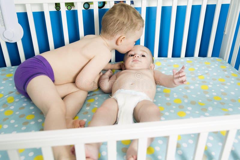小儿床的逗人喜爱的婴孩有他的兄弟的 免版税库存图片