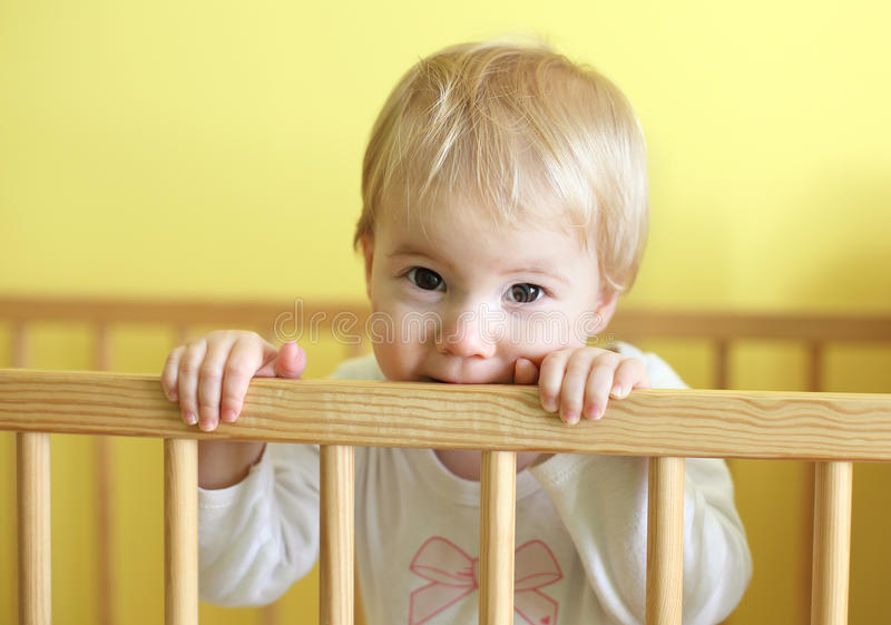 小儿床的年轻逗人喜爱的孩子 库存照片
