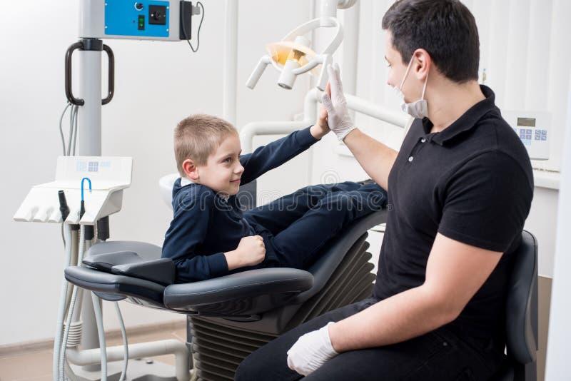 小儿科牙医在牙齿办公室给五个年轻人男孩,祝贺一种成功的治疗的患者 库存图片