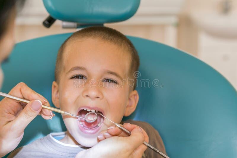 小儿科牙医审查在牙医椅子的小男孩牙在牙齿诊所 审查一点boy& x27的牙医; s 免版税图库摄影