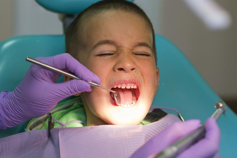 小儿科牙医审查在牙医椅子的小男孩牙在牙齿诊所 有一位牙医的一个孩子a的 库存照片