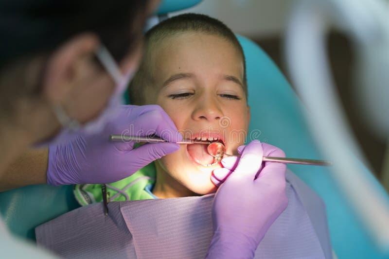 小儿科牙医审查在牙医椅子的小男孩牙在牙齿诊所 有一位牙医的一个孩子a的 免版税库存照片