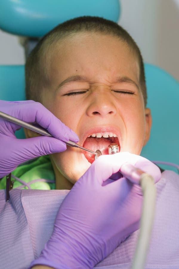 小儿科牙医审查在牙医椅子的小男孩牙在牙齿诊所 有牙医的一个孩子 免版税库存照片