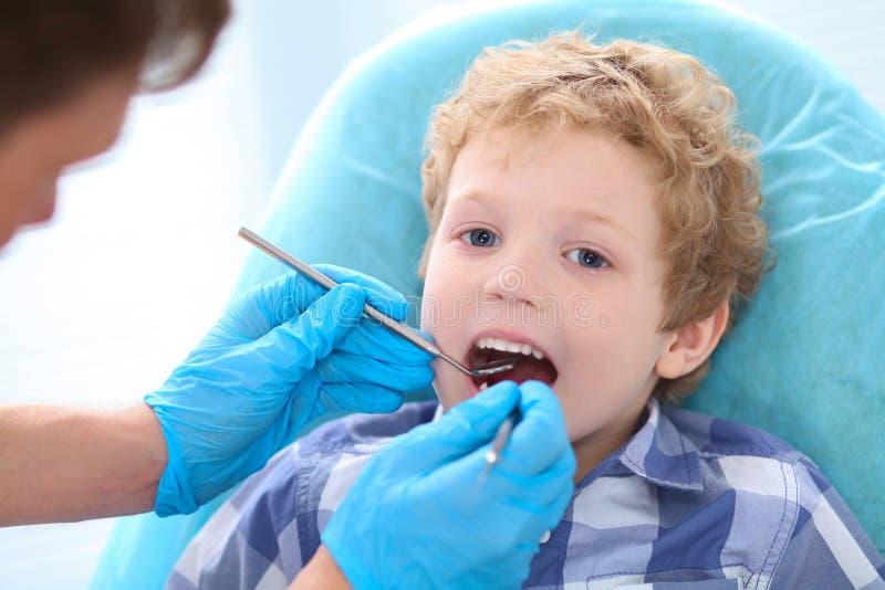 小儿科牙医审查在牙医椅子的小的卷曲男孩牙在诊所 医疗治疗和测试 免版税图库摄影