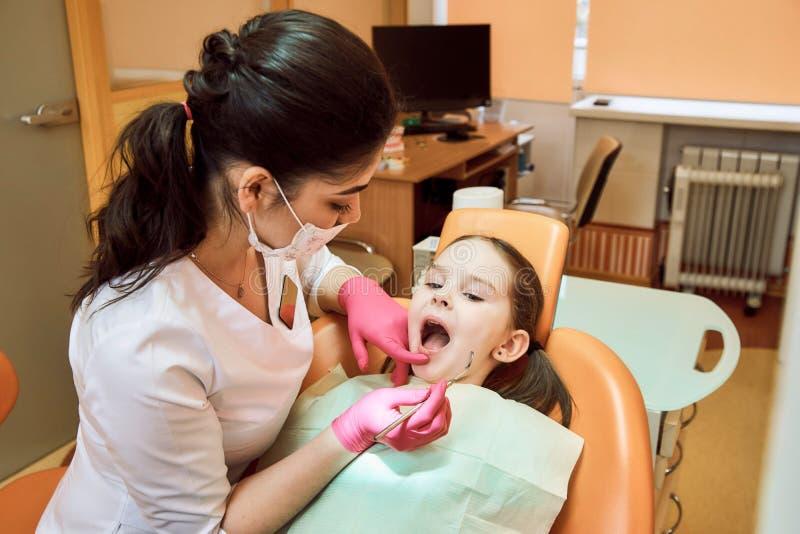 小儿科牙科 牙医对待女孩的牙 免版税库存照片