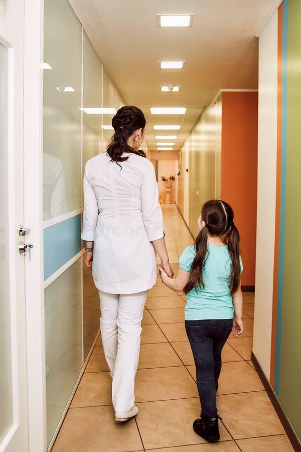 小儿科牙科 牙医带领女孩对待牙 免版税库存图片