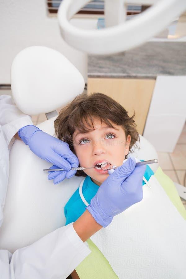小儿科牙医审查在牙医椅子的小男孩牙 免版税库存照片