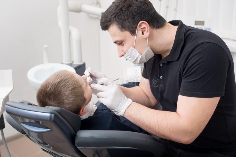 小儿科男孩患者的牙医审查的牙牙齿诊所的使用牙齿工具-探针和镜子 库存照片