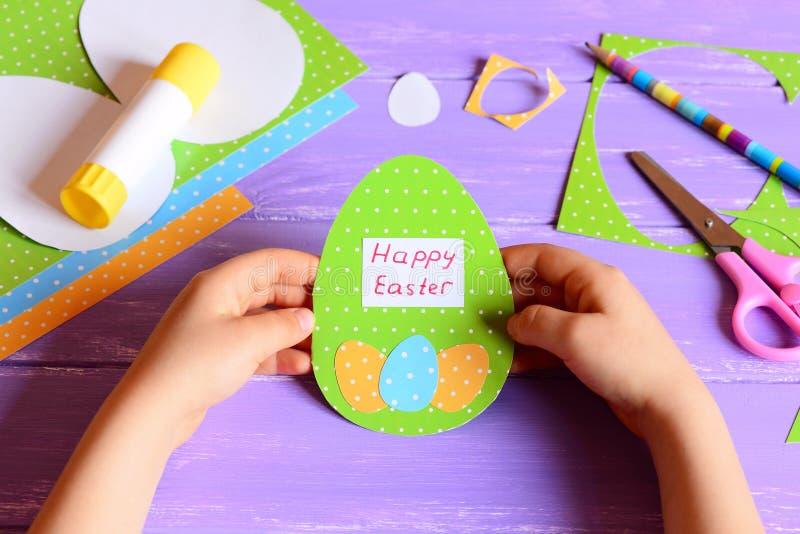 小儿童举行复活节卡片在手上 孩子做了在蛋形状的愉快的复活节贺卡 想象力和创造性 免版税库存照片
