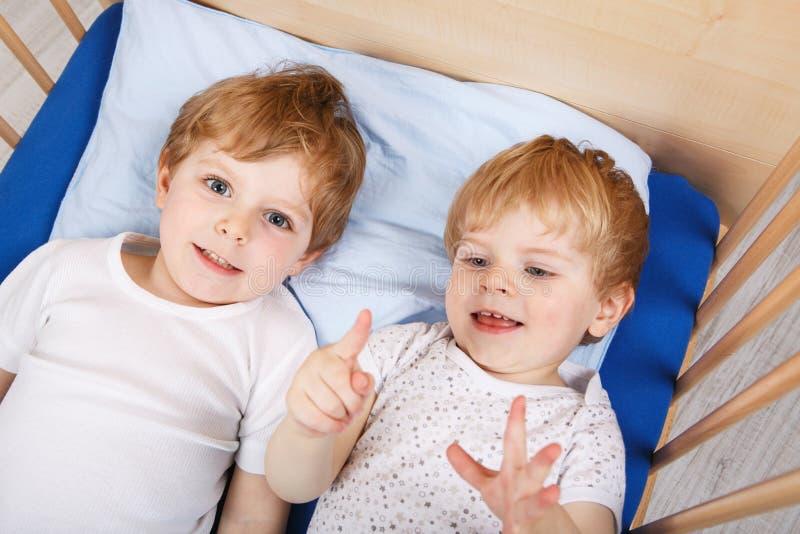 小兄弟姐妹男孩获得乐趣在床在家 免版税库存照片