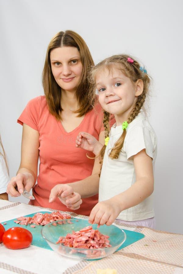 小六岁的女孩帮助母亲烹调在厨房用桌上 免版税库存照片