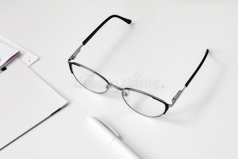 小册子和圆珠笔,说谎在桌上的玻璃 图库摄影