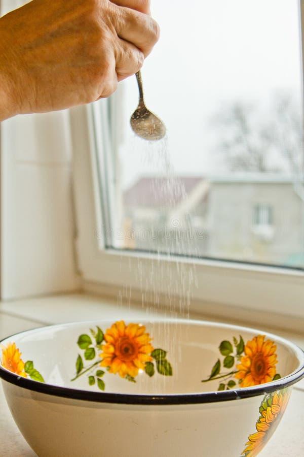 小匙子倒在一个被绘的碗的糖在厨房特写镜头 ?? 免版税库存照片
