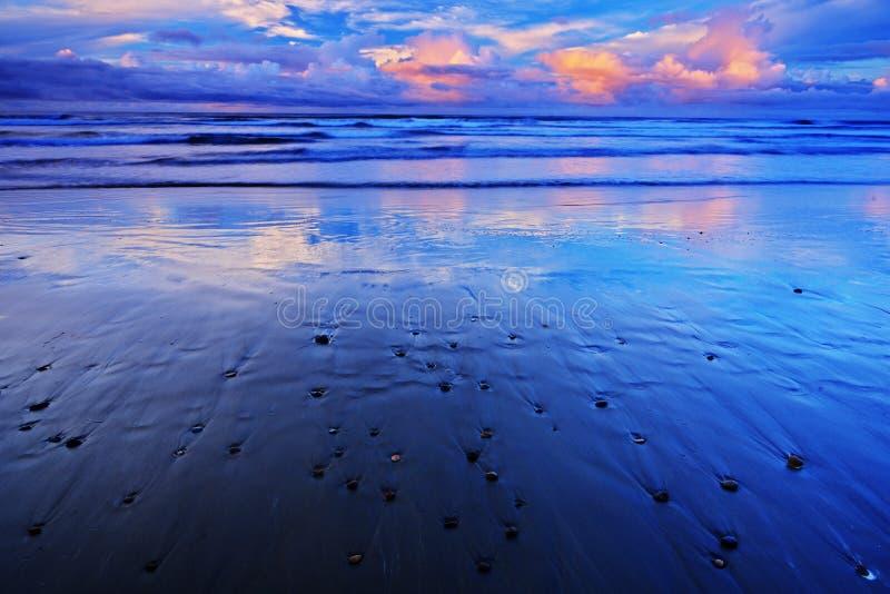 小卵石和沙子靠岸在日出,与深蓝波浪和橙色云彩,哥斯达黎加海岸 图库摄影