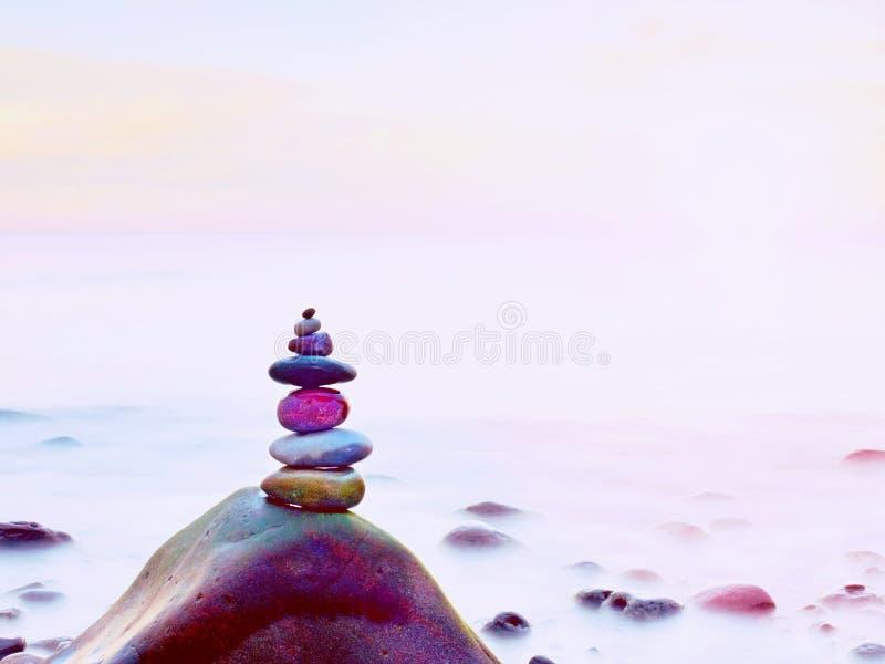 小卵石平衡以被弄脏的海为背景的 在海滩的光滑的大气 库存照片