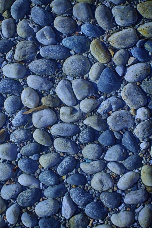 小卵石的蓝色尼斯背景图象,圆的岩石纹理 免版税库存照片
