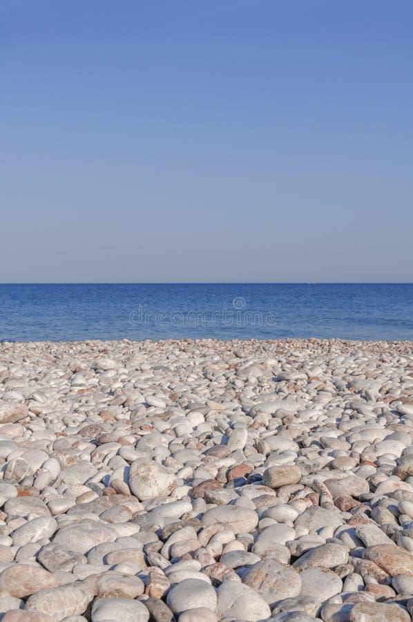 小卵石石海滩和蓝色波浪海有干净的天空的 免版税库存照片