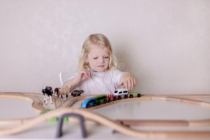 小可爱宝贝男孩3岁喝牛奶用曲奇饼和戏剧在桌上设置的木驻地火车 库存照片