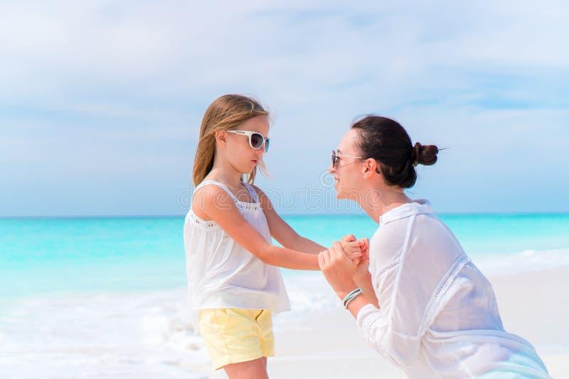 小可爱的女孩和年轻母亲热带海滩的 免版税库存图片
