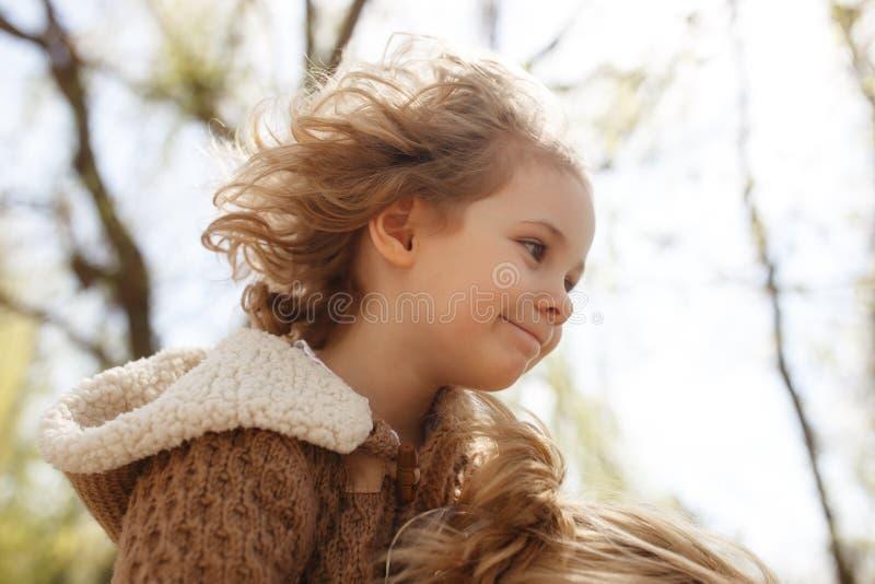 小可爱的女孩坐她的母亲` s担负 室外的秋天 免版税库存图片