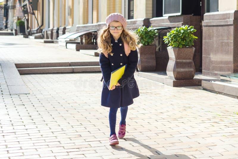 小可爱的女小学生画象有运行到学校,女孩佩带的玻璃盖帽,都市样式backgr的笔记本和背包的 库存照片