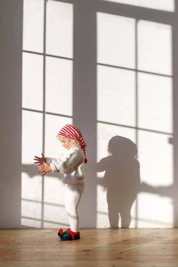 小可爱的金发碧眼的女人相当女性女孩在宽敞的房间站立,佩带白色服装、红色帽子和矮子s鞋子戏剧 免版税库存照片