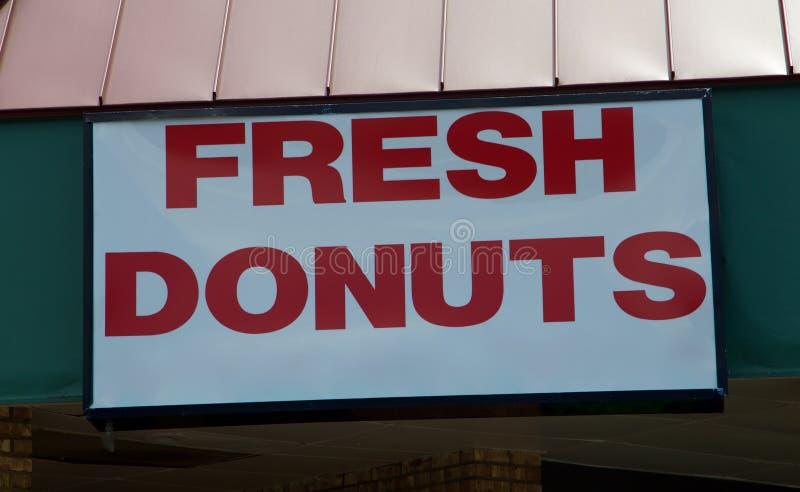 小吃店给新鲜的热的油炸圈饼做广告 免版税图库摄影