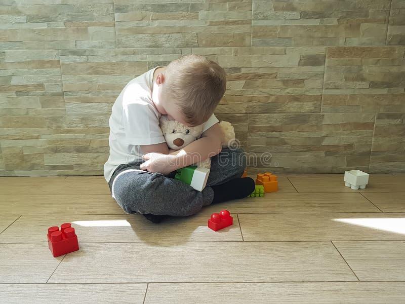小哀伤的男孩坐不快乐地板的柔软块消沉frustratedsadness 库存图片