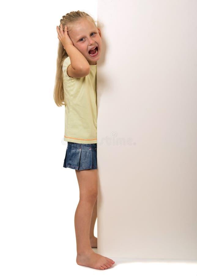 小哭泣的女孩从在白色隔绝的后面横幅偷看  库存图片