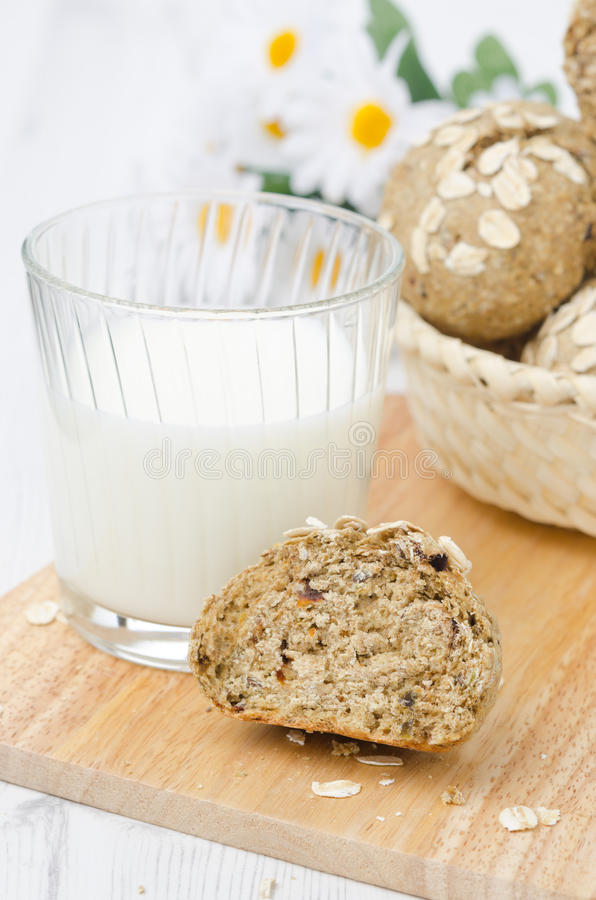 小圆面包全麦与燕麦剥落和一杯牛奶 免版税库存图片