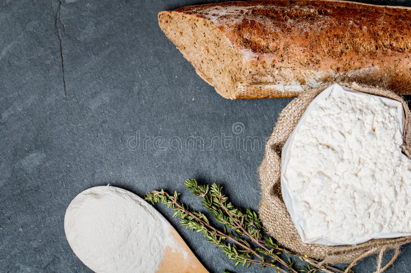 小圆面包或法国长方形宝石和面粉在黑色 库存图片