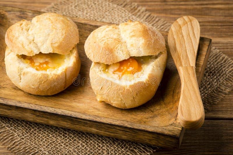 小圆面包烘烤了用菠菜、鸡蛋和乳酪在木背景 库存图片
