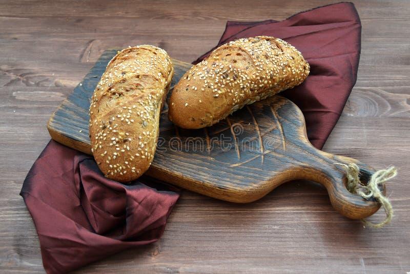 小圆面包用与土气切板的谷物在木桌上 免版税库存图片